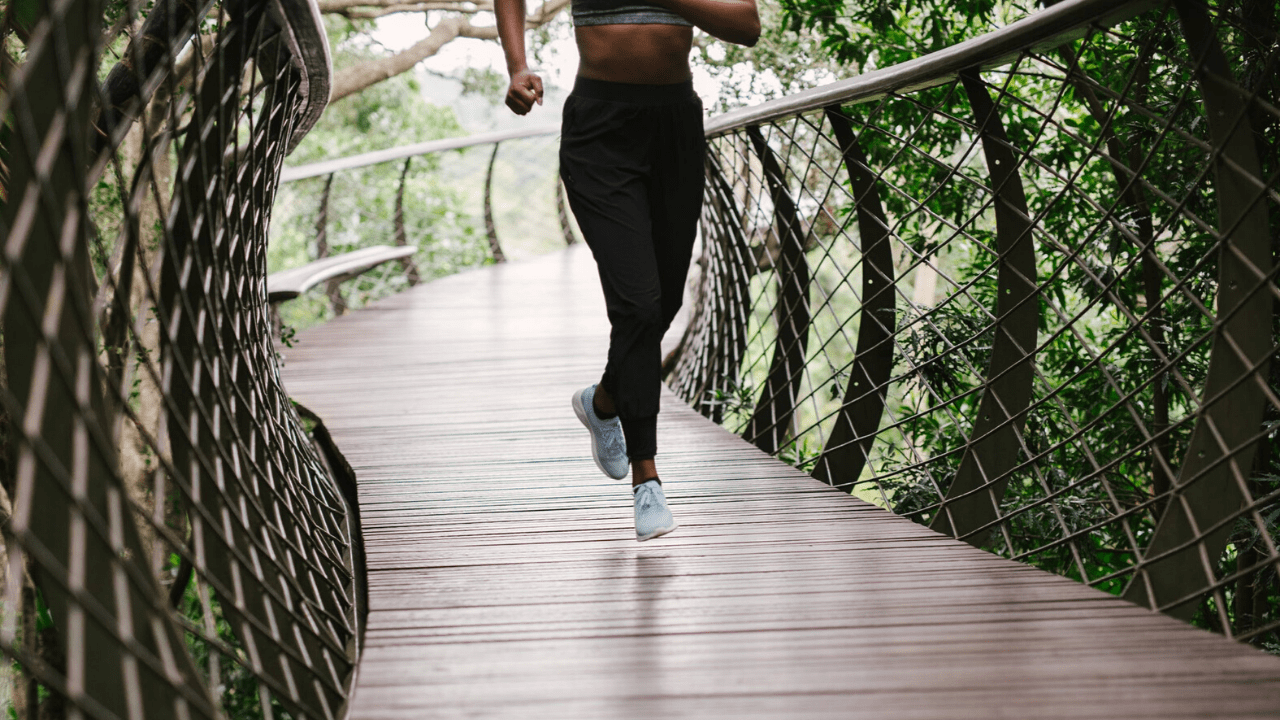 Woman jogging while surrounded by greenery