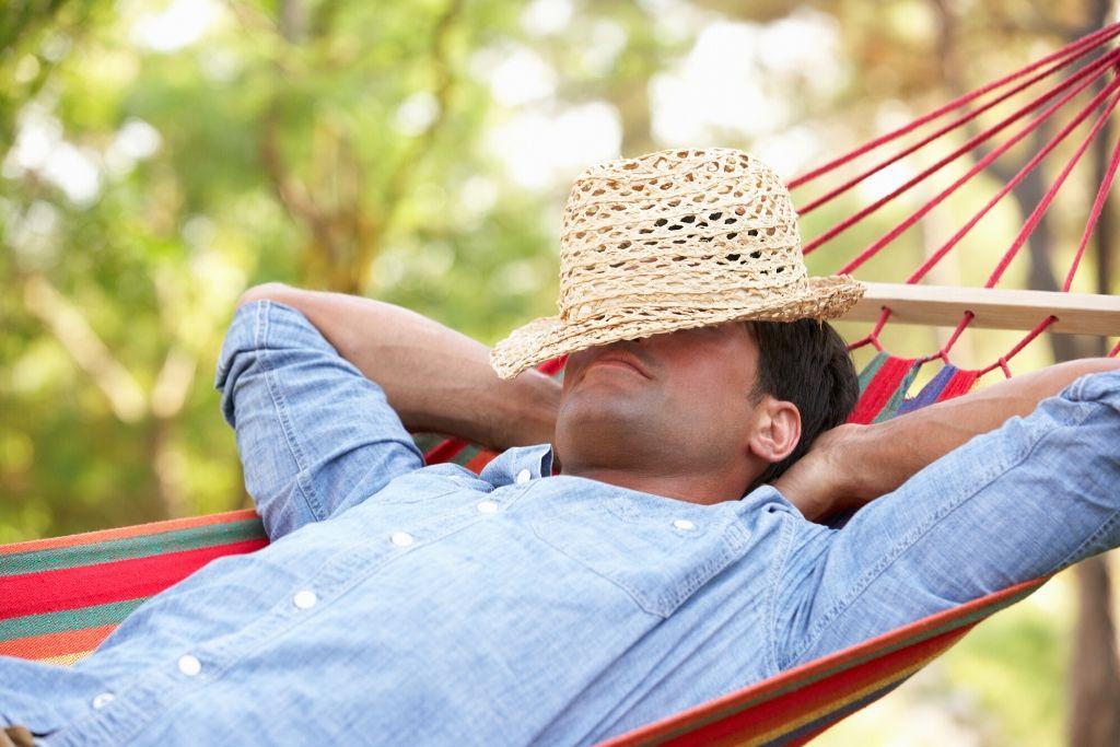 A man sleeping on a hammock outside