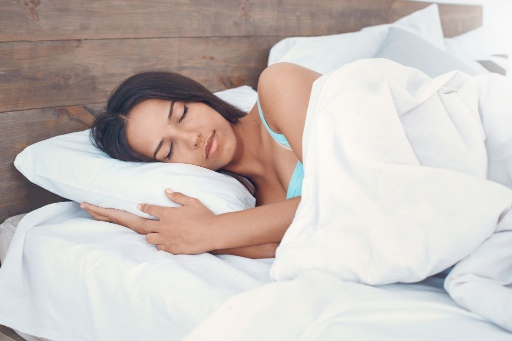 A woman sleeps soundly after taking CBD oil for sleep