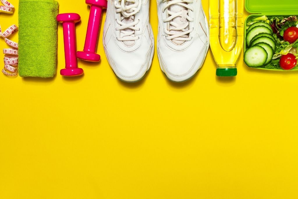 Shoes, weights, and juice laid out on a yellow backdrop.