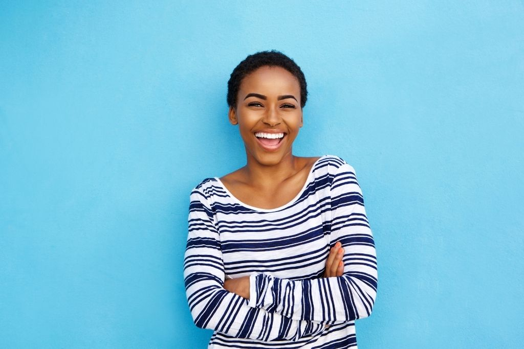 A women smiling in front of a blue background.